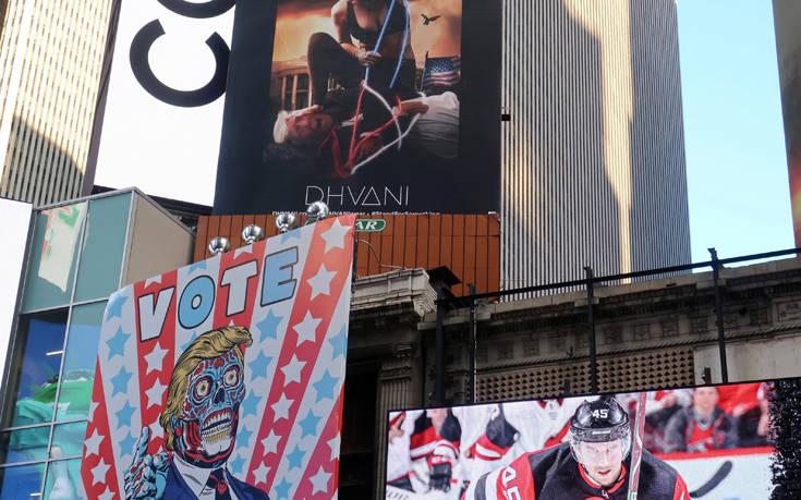Αφίσα στην Times Square δείχνει γυναίκα να πατάει στο κεφάλι τον Τραμπ